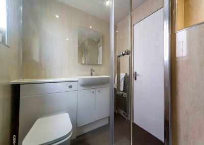 A modern and bright shower room in Grangelea Court, with WC and washbasin.