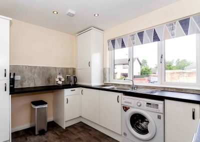 Beautifully refurbished kitchen in Grangelea Court with cooker, washing machine, dishwasher, microwave, all crockery and utensils – available to let at Grangemouth Property Lets.
