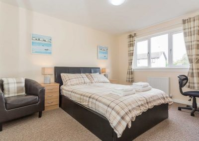 Welcoming and comfortable bedroom in Grangelea Court with flat screen TV and double bed, desk and chair.